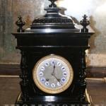 Реставратор отреставрировал корпус каминных черных часов.